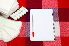 Notepad, red pen for notes and woman hygiene protection, menstruation sanitary pads and cotton tampons on the plaid at home. Prote Royalty Free Stock Image