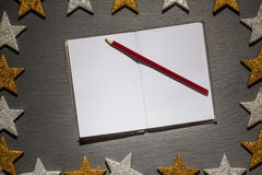 Notepad with red pencil on slate background, christmas frame Stock Photos