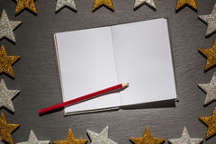 Notepad with red pencil on slate background, christmas frame Royalty Free Stock Images