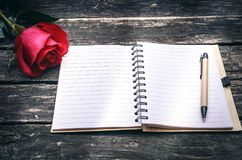 Notepad and red rose flower. Love confession. Red rose flower and notepad with blank pages on aged wooden table background. Greeting card design Stock Photography