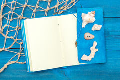 Notepad with shells on blue boards, copyspace Royalty Free Stock Photos