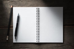 Notepad. Small notepad with pen and pencil on rustic wood background with low key scene Stock Images