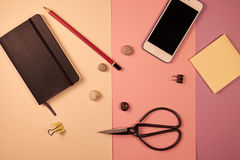 Notepad smartphone, blyertspenna, stickes på rosa bakgrund Arkivfoton