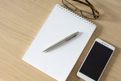 Notepad, smartphone, glasses and sliver ballpen. On wooden office desk. Image with copy space. Selective focus stock photos