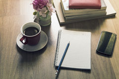Notepad, smartphone, pen and cup of coffee on wood table royalty free stock images