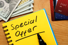 Notepad with special offer. Notepad with special offer on a wooden table Royalty Free Stock Images