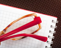 Notepad, spectacles and backing Royalty Free Stock Image