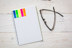 Notepad and spectacles on white boards Stock Photo
