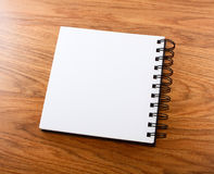 Notepad with a spiral binding on a wooden background. Royalty Free Stock Photography