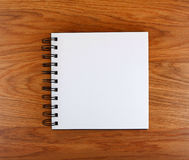 Notepad with a spiral binding on a wooden background. Notepad with a spiral binding on a wooden background Royalty Free Stock Photos
