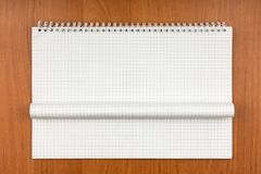 Notepad on a spiral with a curled sheet lying on a table. Stock Photography