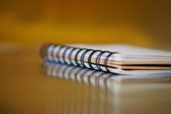 Notepad with a spring on a golden background with reflection. Work in the office. Research and training stock photography