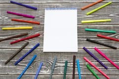 Notepad on a spring surrounded by colored markers. royalty free stock image
