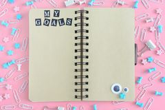 Notepad on springs with brown pages. The inscription My Goals. Stationery is in disarray. The asterisks and puppet eyes. Are chaotically scattered on a pink stock image