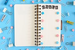 The notepad on the springs lies open. Next to the mess office supplies. The white pages of the notebook contain the. Inscription GOALS and pink and blue Royalty Free Stock Image