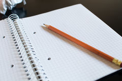 A notepad with squares and an orange pencil. On top left a crump Royalty Free Stock Photo