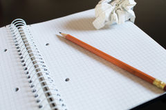 A notepad with squares and an orange pencil. On top right a crum stock photos