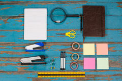 Notepad, stapler, pins, sellotapes, diary, sticky notes, ruler and pens. On wooden plank Stock Images