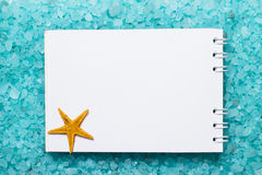 Notepad and starfish on bath salt background Stock Photos