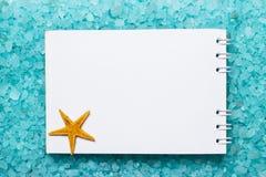 Notepad and starfish on bath salt background Stock Photos