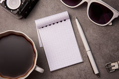 Notepad, sunglasses, pen and cup on the table Royalty Free Stock Image