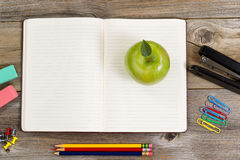 Notepad with supplies and apple snack for school or office on ru Royalty Free Stock Image