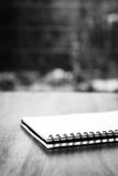 Notepad on a table. Black and white image of a notepad on a table in front of a window Royalty Free Stock Image