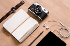 Notepad, tablet, earphones, camera watch and pen on wooden table. Opened notepad with white blank pages, tablet computer with earphones, old camera watch and pen Royalty Free Stock Image