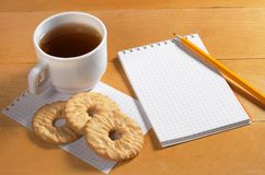 Notepad, tea and cookies Royalty Free Stock Images