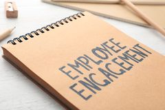 Notepad with text EMPLOYEE ENGAGEMENT. On table Stock Photos