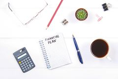 Notepad with the text: financial plan. White table with calculator, cactus, note paper, coffee mug, pen, glasses. Royalty Free Stock Image