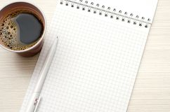 Notepad for text. White pen, Cup of coffee. Close-up royalty free stock image
