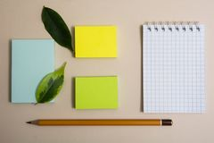 Notepad three different colored sticky papers and two pencils on a light background royalty free stock image