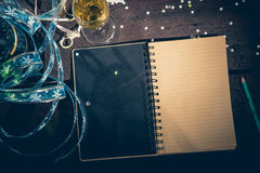 Notepad to write New Year`s resolutions. Open notepad on the old table ready to write New Year`s resolutions, Champagne and glass, confetti. New years concept Stock Photo