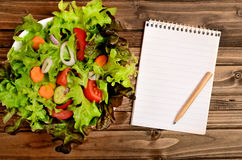 Notepad and vegetable salad Royalty Free Stock Image