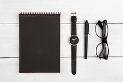 Notepad, watches, pen and reading glasses on the desk Stock Photography