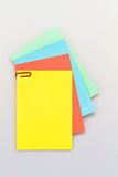 Notepad on white background series. Colorful notepad arrangement on white background with yellow paper on top Stock Photo
