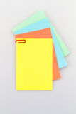 Notepad on white background series II. Colorful notepad arrangement on white background with green paper at the back Stock Image