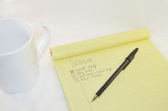 Notepad with White Coffee Mug and Black Ballpoint Pen on a White Background Stock Photos