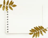 Notepad with white empty pages and golden leaves. On white background. Flat lay. Top view Royalty Free Stock Image