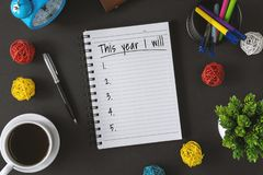 Notepad with wish list and coffee cup. New year hope and resolution concept. Notepad with wish list and coffee cup. New year`s hope and resolution concept stock photos