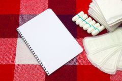Notepad and woman hygiene protection, menstruation sanitary pad and cotton tampons on the plaid at home. Protection for woman crit Royalty Free Stock Images