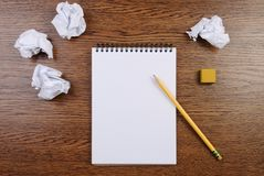 Notepad on a wooden table and crumpled sheets around. Flat lay. Notepad, pencil, eraser and crumpled sheets around on brown wooden table. Flat lay. Writing royalty free stock photography