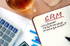 Notepad with words CRM customer relationship management concept. Notepad with words CRM customer relationship management concept and marker Stock Photo