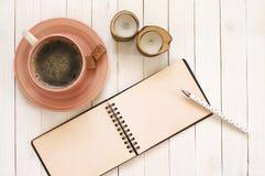 Notepad z piórem, kawą i świeczkami na biurku, obrazy stock