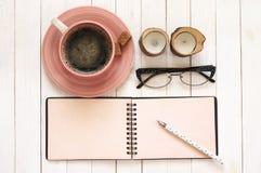 Notepad z piórem, kawą, szkłami i świeczkami na biurku, obrazy stock
