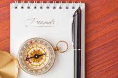 Notepad z ręcznie pisany słowo trendami, kompas i Zdjęcia Royalty Free