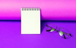 Notepad z szkłami na neonowym purpurowym tle zdjęcie stock