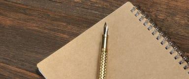 Notepad Z Złocistym fontanny piórem Na Starym drewno stole Obrazy Royalty Free