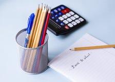 Notepaden, blyertspennorna och räknemaskinen arkivfoto